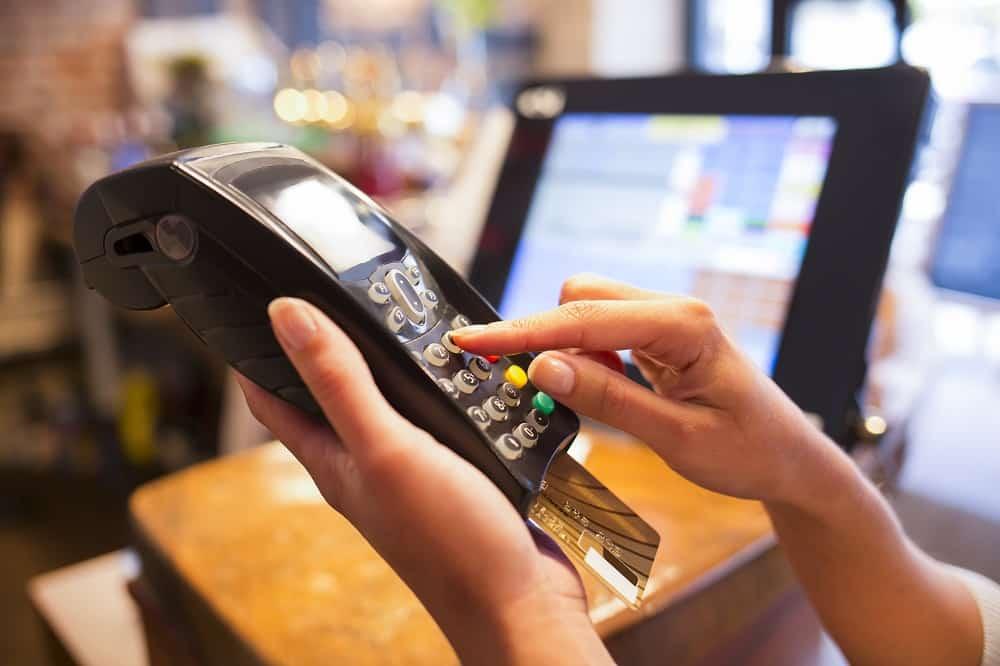 Femme tapant son code bancaire sur un tpe