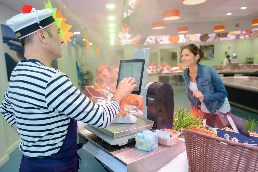 Cliente et vendeur caisse poissonnerie