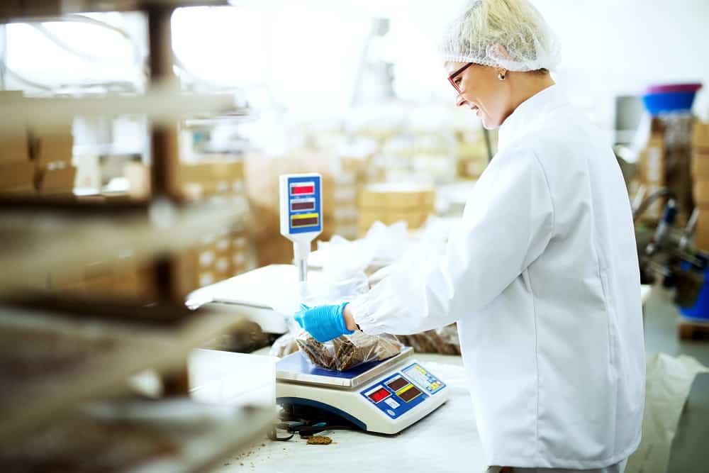 Employé d'usine mesurant les collations agroalimentaire.